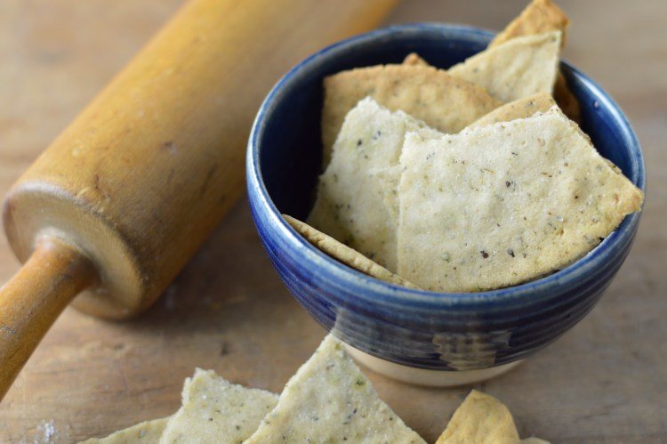 Closeup of Cassava Lavosh Crackers in a blue pottery bowl next to an old-fashioned rolling pin