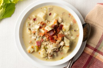 Steaming bowl of AIP Clam Chowder garnished with crispy bacon on a plate with an old spoon