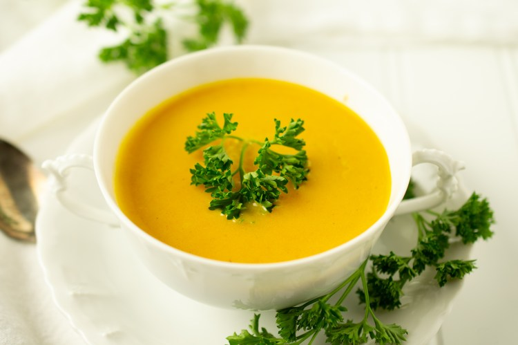 Irish Carrot Soup in an old-fashioned two-handled white bowl surrounded by parsley