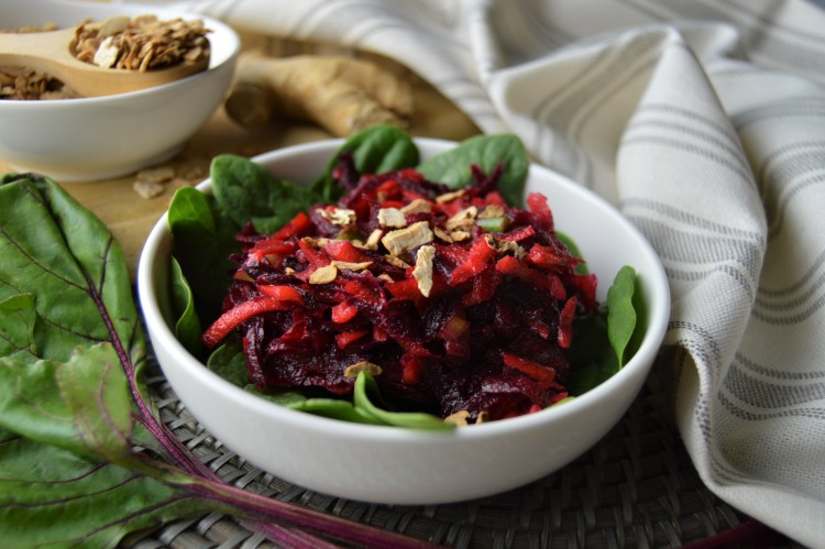 Beet Carrot Salad with Orange Ginger Dressing atop baby spinach greens topped with toasted tigernuts