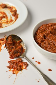 AIP Spaghetti Sauce smeared on a plate, slopped on a table, in a bowl and on a spoon.