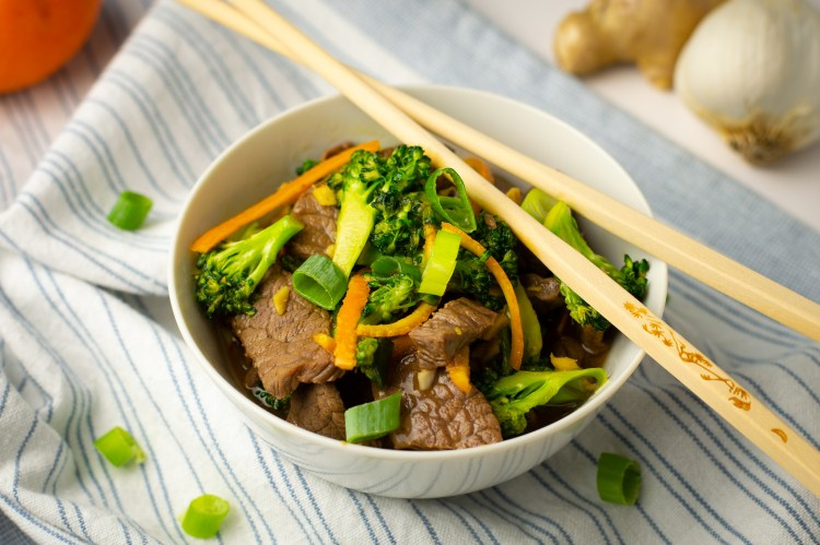 Orange Peel Beef and Broccoli in a white bowl with bamboo chopsticks