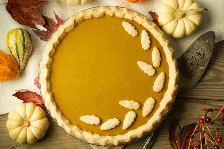 Full pumpkin pie with cut out leaves of crust on top set in a Thanksgiving scene