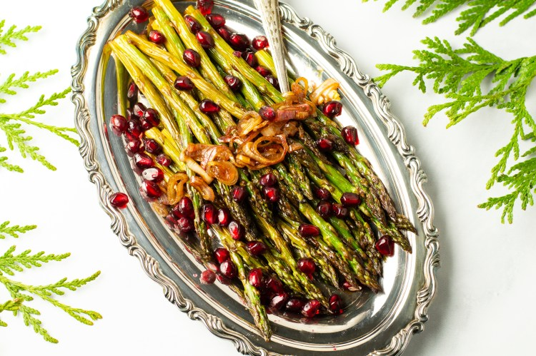 pomegranate roasted asparagus on a silver platter topped with pomegranate arils and roasted shallots
