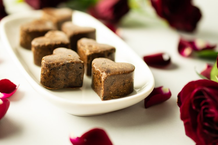 Heart-shaped Flavored Carob Candies on a dish romantically set midst roses and rose petals