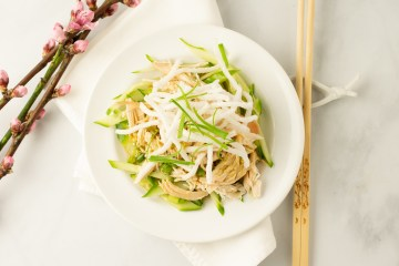 Chopsticks are perched next to a bowl of shredded cucumbers topped with shredded chicken, sauce and fried sweet potato noodles next to a branch of cherry blossoms