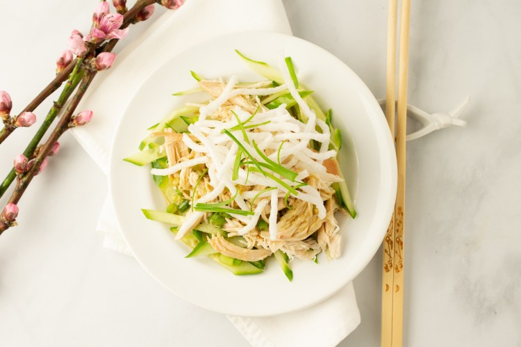 Chopsticks are perched next to Chicky Chicky Bang Bang, a bowl of shredded cucumbers topped with shredded chicken, sauce and fried sweet potato noodles next to a branch of cherry blossoms