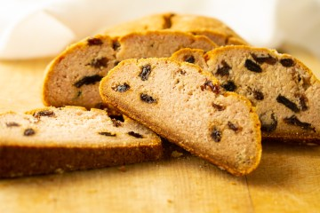 Slices of Irish Soda Bread (AIP/Paleo) studded with raisins in front of a half cut loaf
