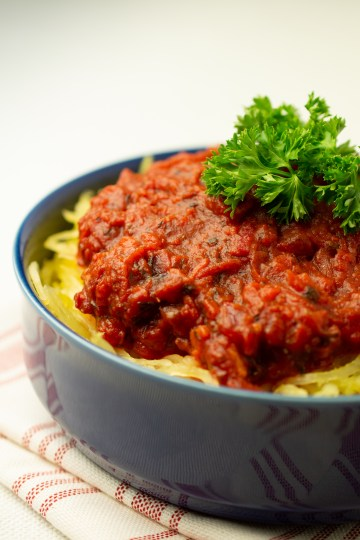 Closeup of No-nightshade Amatriciana Sauce atop spaghetti squash and garnished with parsley