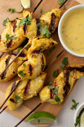 Easy Chicken Satay on a bamboo cutting board with cut limes, chopped cilantro and dipping sauce