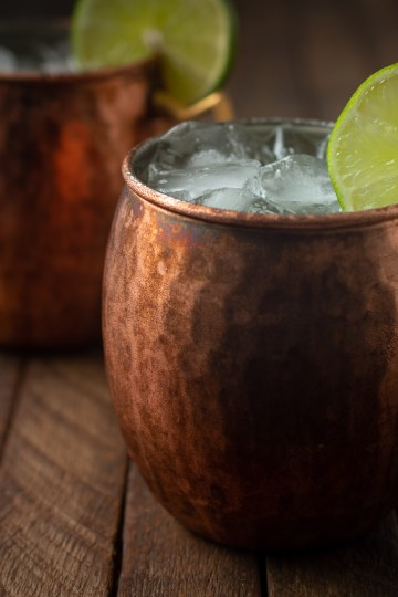 Scene of two copper mugs with lime wheels holding No-alcohol Moscow Mules