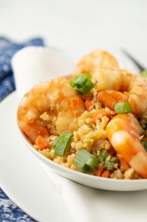 Closeup of Shrimp Fried Rice in a bowl on a napkin and plate with slender chopsticks nearby