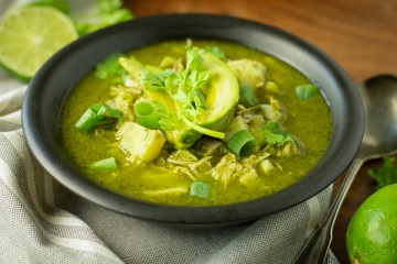"Black bowl with ""Pozole"" Verde (Paleo/AIP) garnished with avocados, cilantro, and green onions"