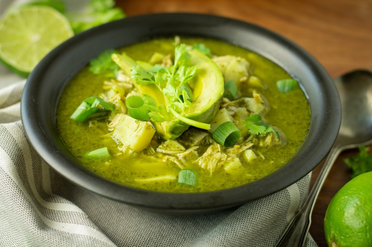 """Black bowl with """"Pozole"""" Verde (Paleo/AIP) garnished with avocados, cilantro, and green onions"""