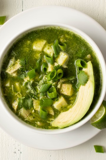Landsape Flatlay of Pozole Verde (AIP/Paleo) garnished with green onions, cilantro and avocado slice