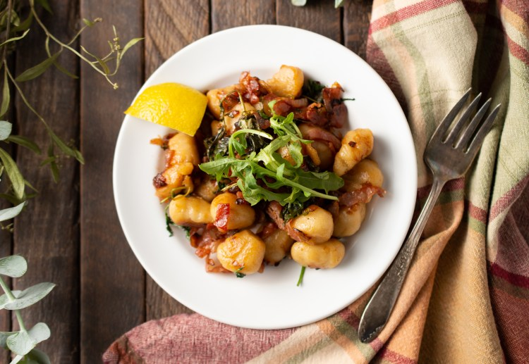 Flatlay of Pan-seared Cauliflower Gnocchi (Paleo/AIP) garnished with fresh arugula and a wedge of lemon