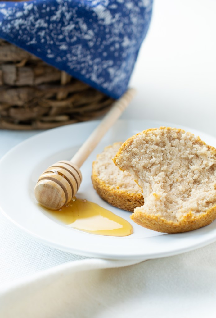 Honey Biscuits with honey dripper on a plate next to a basket of biscuits