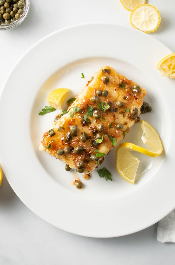 Flatlay of Halibut with Lemon Caper Sauce on a white plate with random pieces of lemon nearby and a small dish of capers