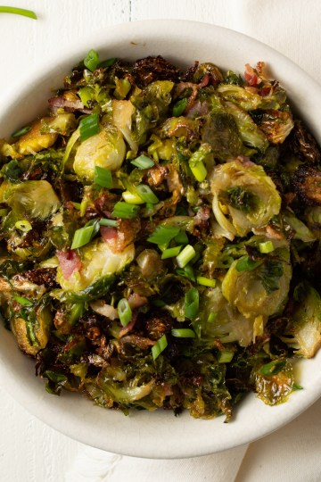 Overhead view of a bowl of Maple Bacon Brussels Sprouts, garnished with green onions, on a rustic, white wooden background