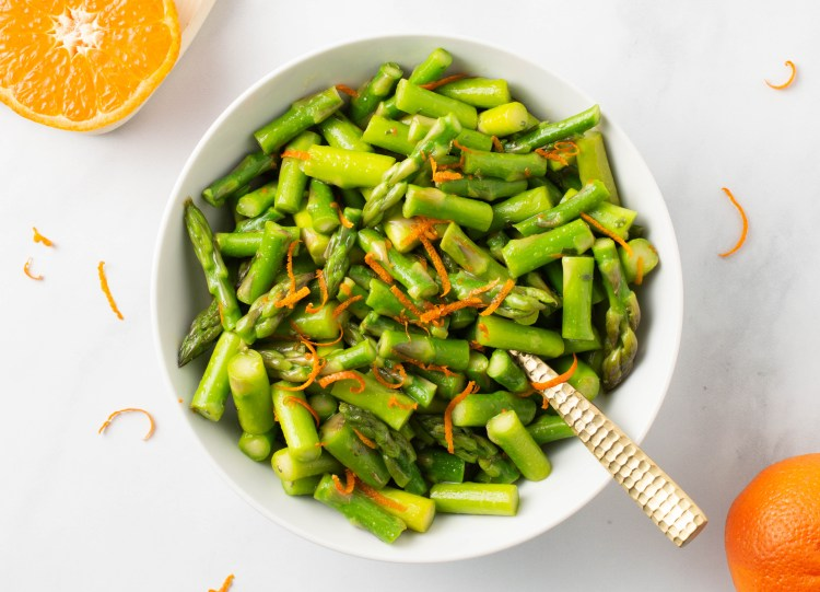 One-inch pieces of Spring Orange Asparagus (AIP/Paleo) in a bowl, garnished with curls of orange zest on a marble background with a sliced orange nearby.