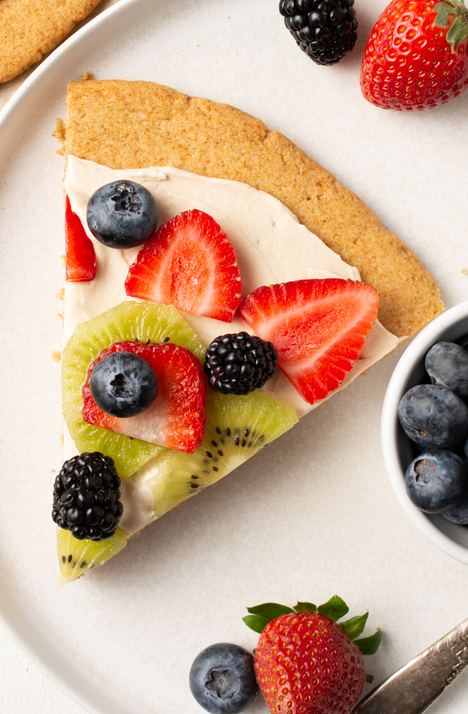 Flatlay of Vanilla Cookie Pizza (AIP/Paleo) garnished with cut strawberries, blackberries, blueberries, and kiwi on a white plate with extra fruit on the side