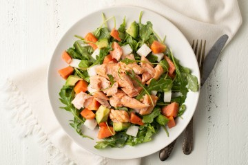 Overhead view of Tropical Salmon Salad w/Vanilla Citrus Dressing. The plate sits on a distressed white background and a cream-colored napkin. A fork and knife are nearby.