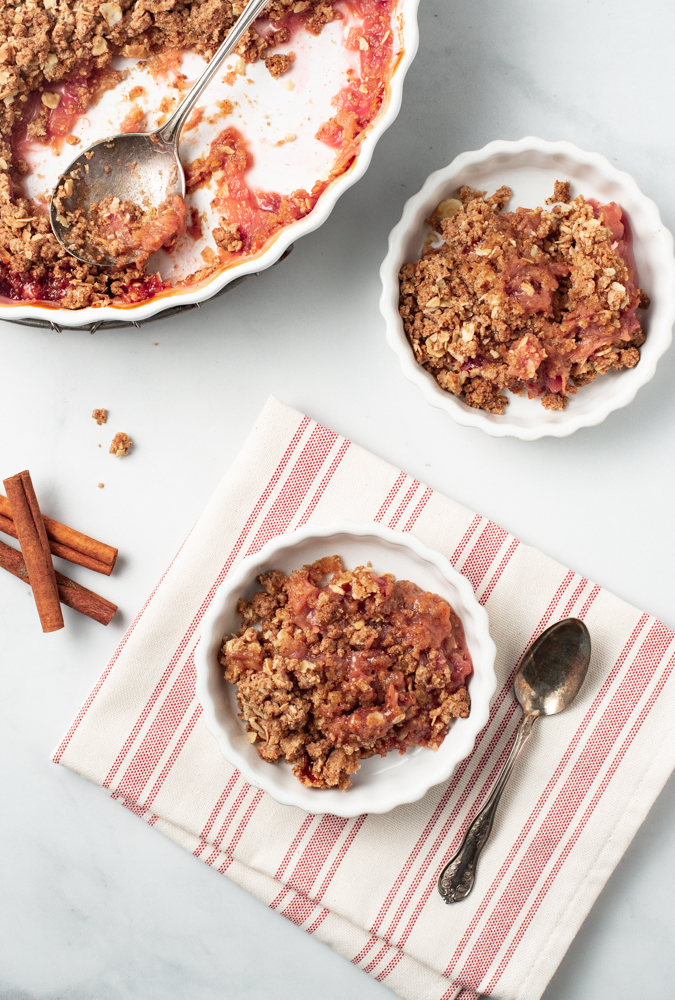 Portrait orientation of a scene of Rhubarb Crisp (Paleo/AIP) with the serving dish and two smaller fluted dishes with servings in them. Cinnamon sticks and crumbs are on the surface nearby. One of the servings sits on a striped towel with a spoon.