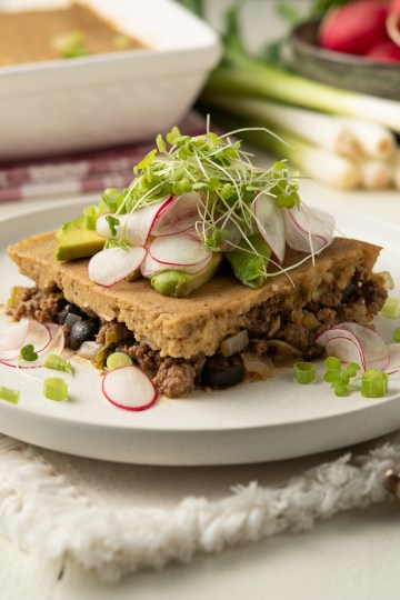 Table scene with Gluten Free/Corn Free Tamale Pie in both a casserole dish and on a plate, garnished with avocado slices, radish slices and micro greens