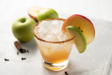 Landscape view of Apple Sage Splasher Mocktail on a slab of marble. The drink is rimmed with cinnamon and coconut sugar, and garnished with green and red apple slices.