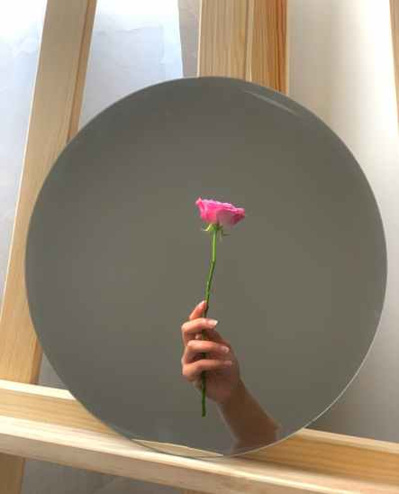 mirror reflecting tender hand with pink rose