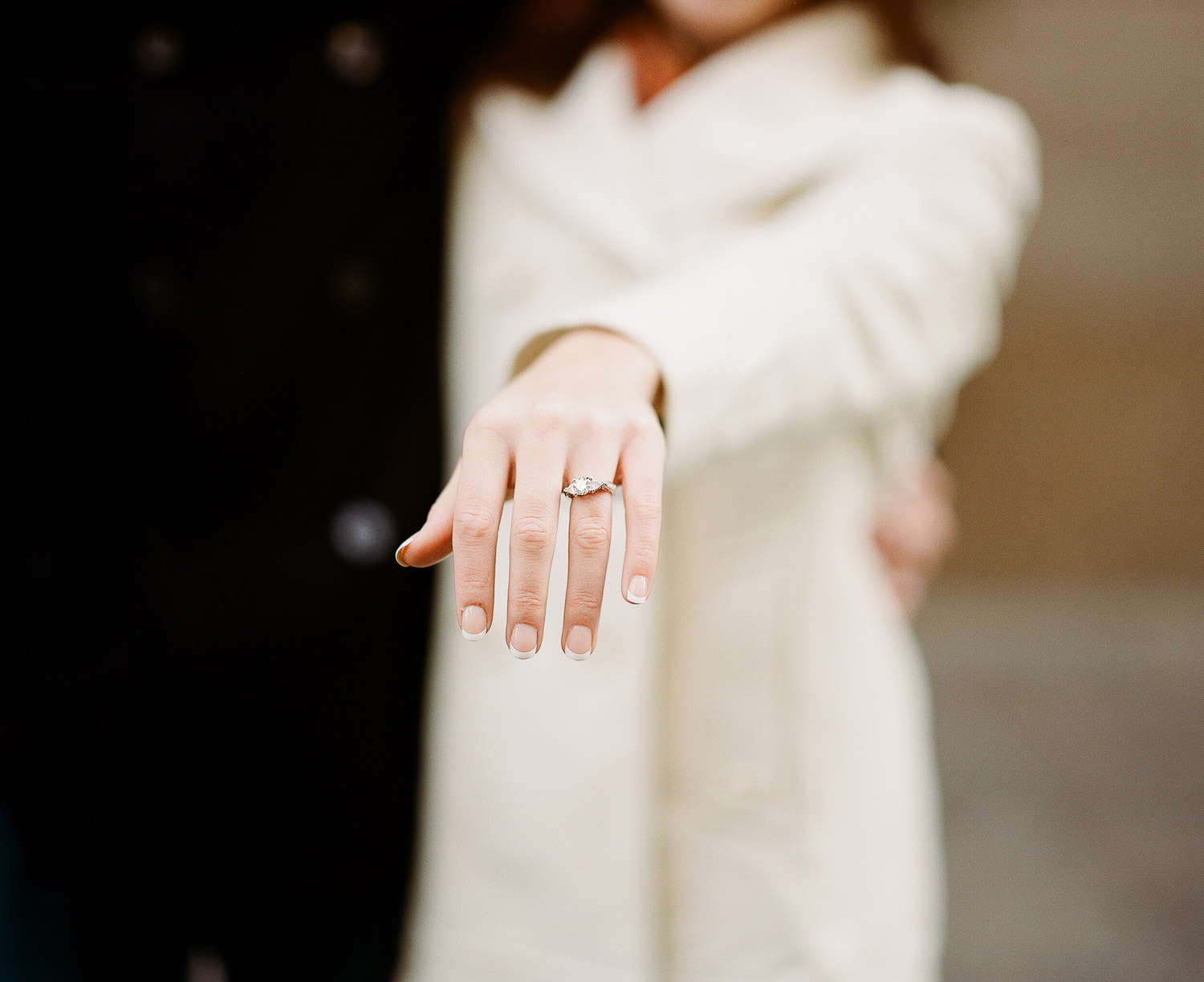 engaged couple with bride showing ring