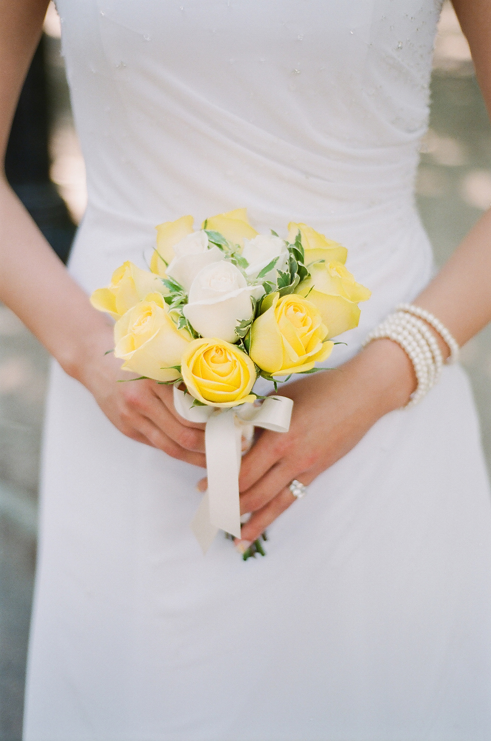 bride holding yellow and white flowers