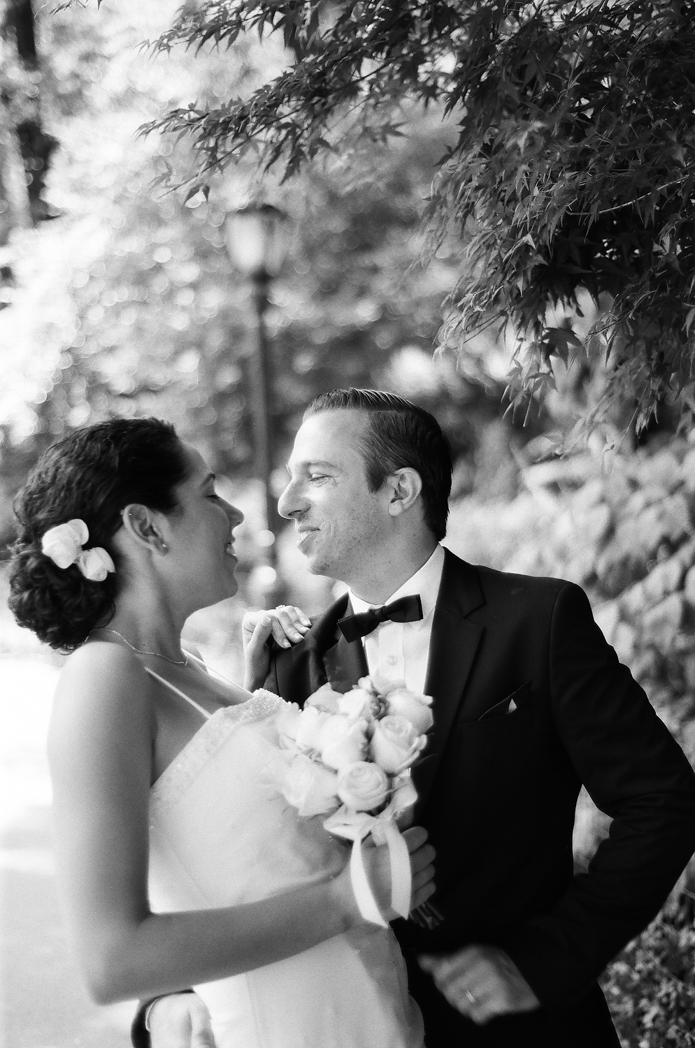 black and white film photo of bride and broom looking at each other in park