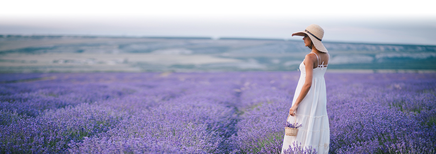 Woman in big hat and white sundress stands in a field of purple wildflowers