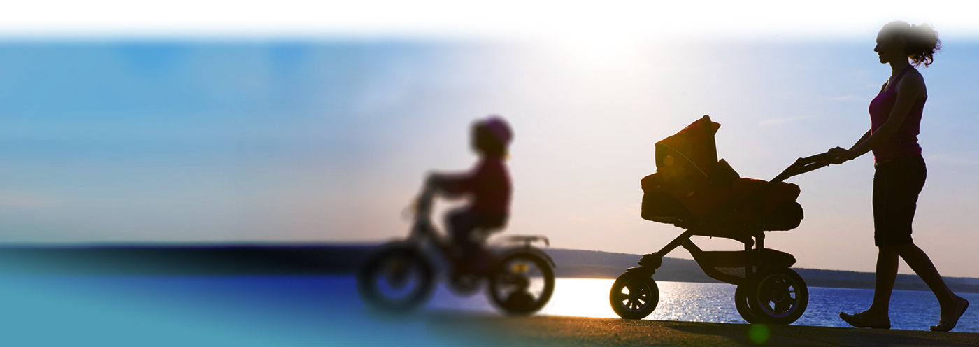 Silhouette of a child on a bike and a mom pushing a stroller on the beach