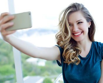 Young woman smiles and takes a selfie