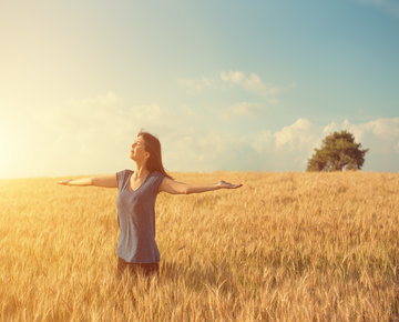 Woman stretches arms in a wheat field under a clear blue sky