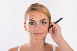 Portrait of young woman undergoing facelift surgery over white background