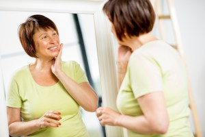 older woman looking at her face with a smile into the mirror