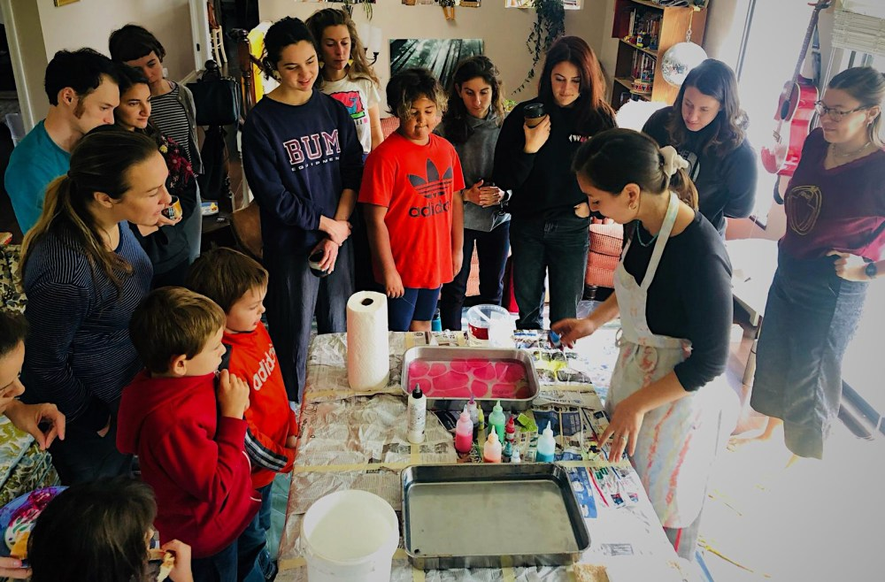 photo of marbling workshop with crowd around Dora Prieto who is mixing red and pink paint on the surface of water in a tray