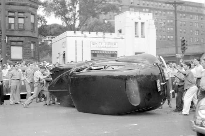 Group of young white men turn a car on its side during Detroit riots of 1943