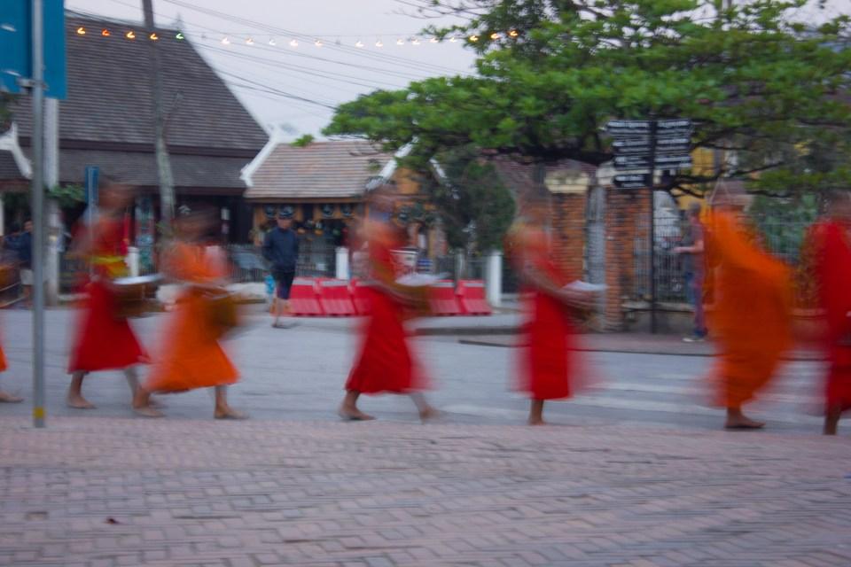 Monniken halen hun almen op in Luang Prabang