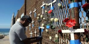 """TIJ10214195. Integrantes del grupo """"Ángeles Sin Fronteras"""" en apoyo a los migrantes, colocaron cruces y flores en la malla metálica que divide a México y Estados Unidos, en el evento, """"amor sin fronteras"""", con motivo del festejo del Día de San Valentín. Hoy en playas de Tijuana. NOTIMEX/FOTO/EDUARDO JARAMILLO/EJC/HUM/"""