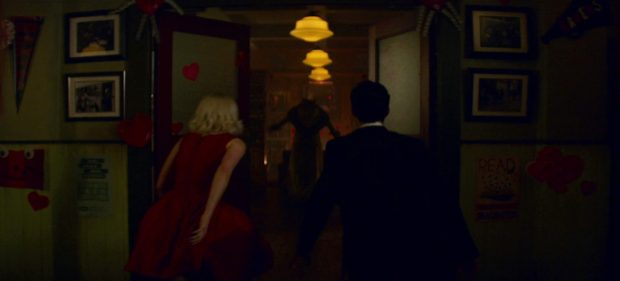 The silhouette of a werewolf approaching Sabrina and Nicholas from the far end of a hallway.