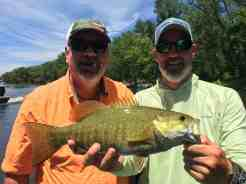 Fishing guide holding a smallmouth bass