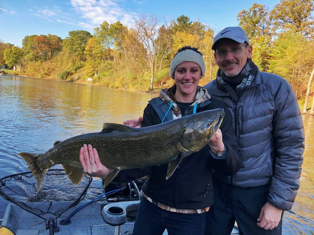 A father and daughter holding a salmon in a West Michigan River