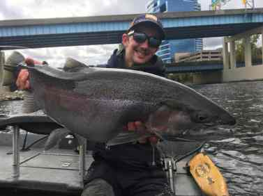 Man holding a steelhead he caught fishing in downtown Grand Rapids