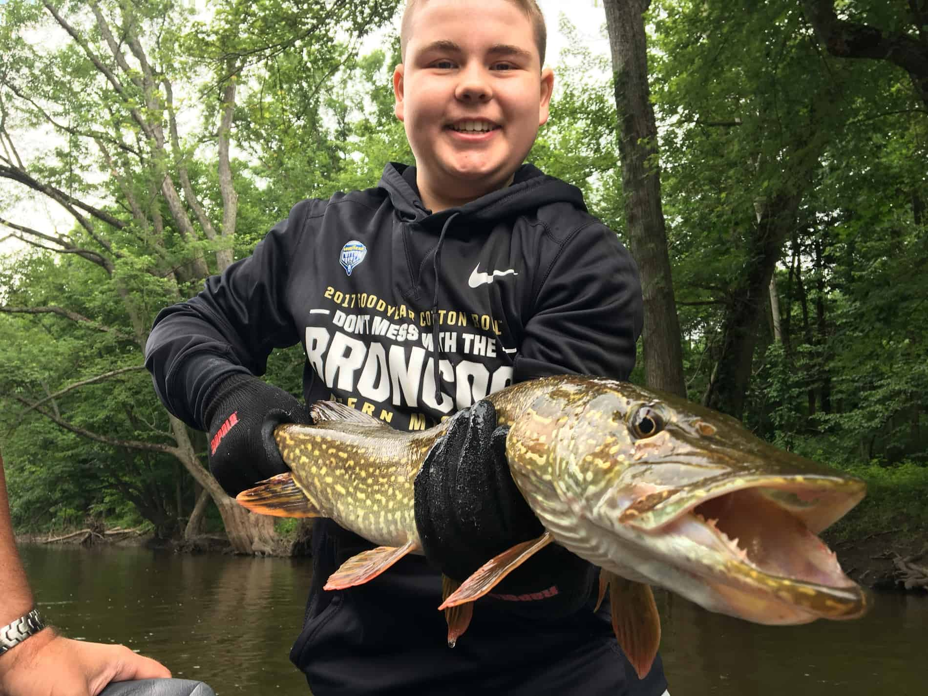 Young man holding a northern pike