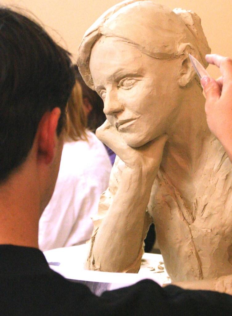 Photo d'un élève du cours de modelage de l'Atelier Werle, Montrouge, faisant un portrait en faïence blanche.