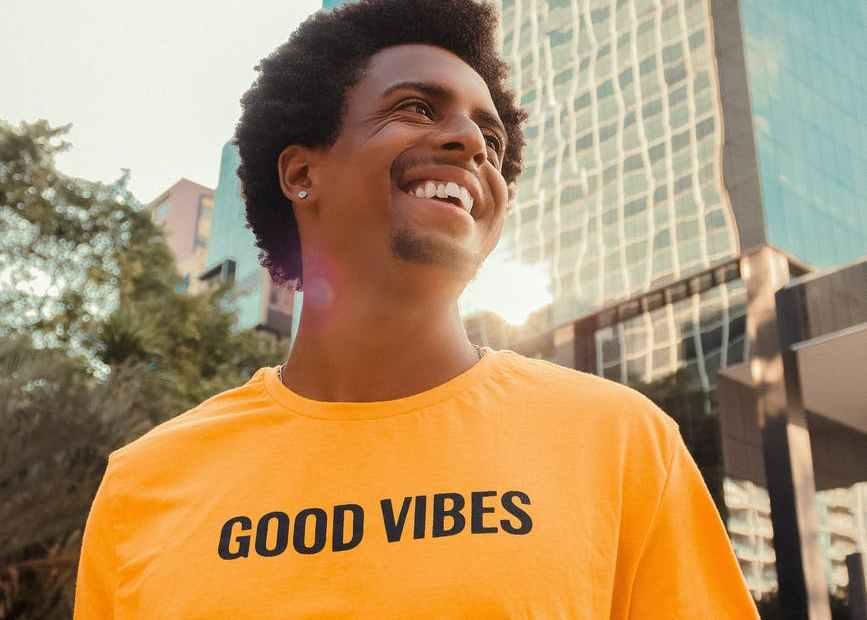 black happy man smiling near modern building